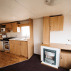2011 Delta Santana 28ft x 12ft - 2 bed for sale at Castle Cove Caravan Park in Abergele North Wales - Kitchen and Gas Fire View
